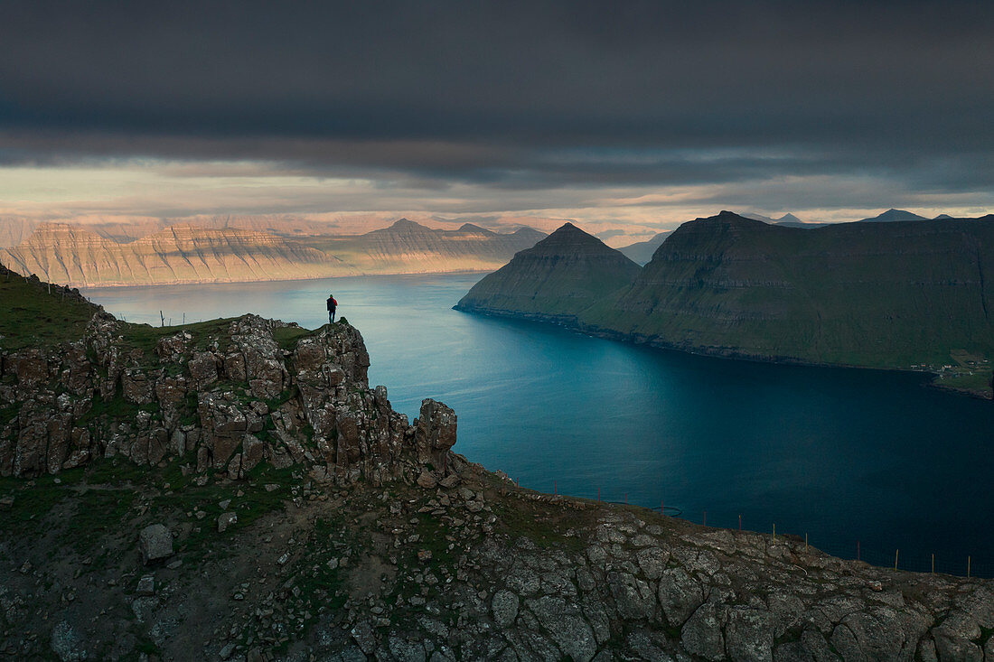 Wanderer am Hvithamar nahe dem Ort Gjogv auf der Färöer Insel Eysturoy mit Panoramablick über Fjord bei Sonnenuntergang