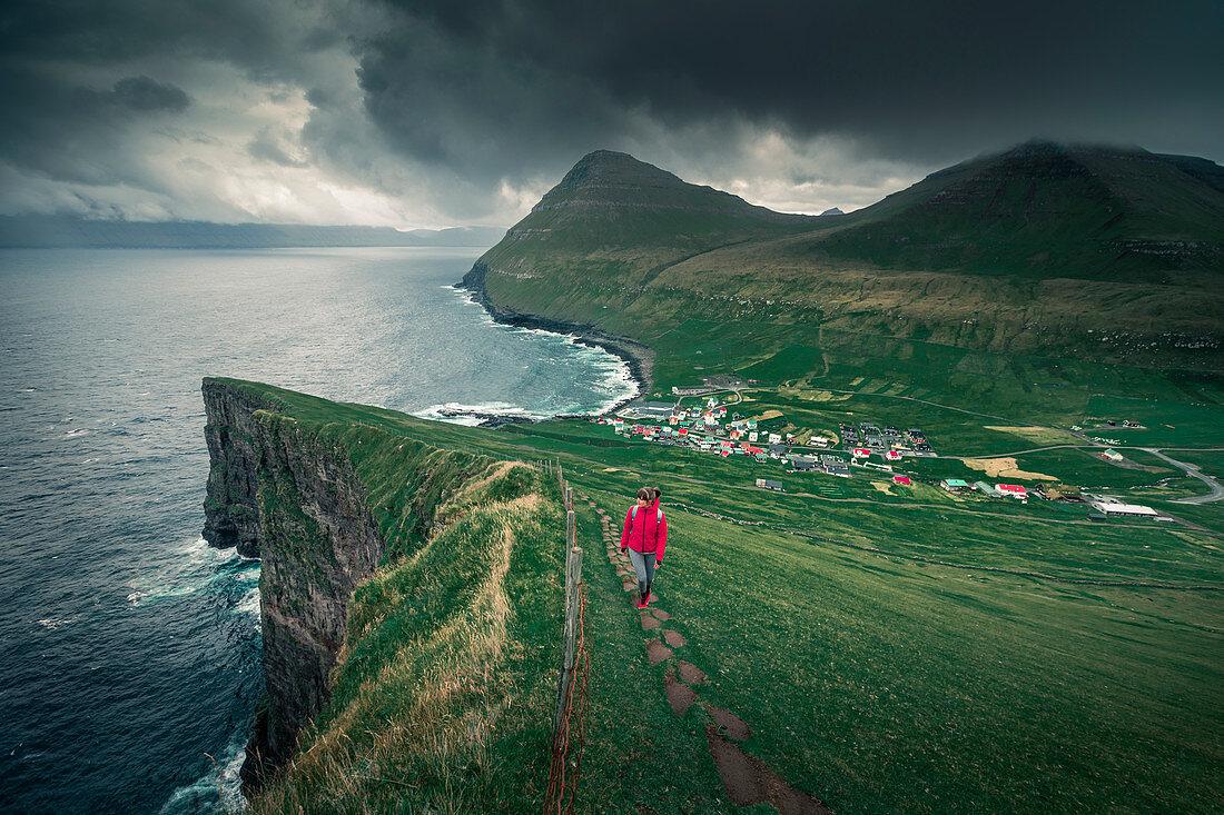 Frau wandert zum Dorf Gjogv auf Eystruoy mit Schlucht, Meer und Bergen, Färöer Inseln