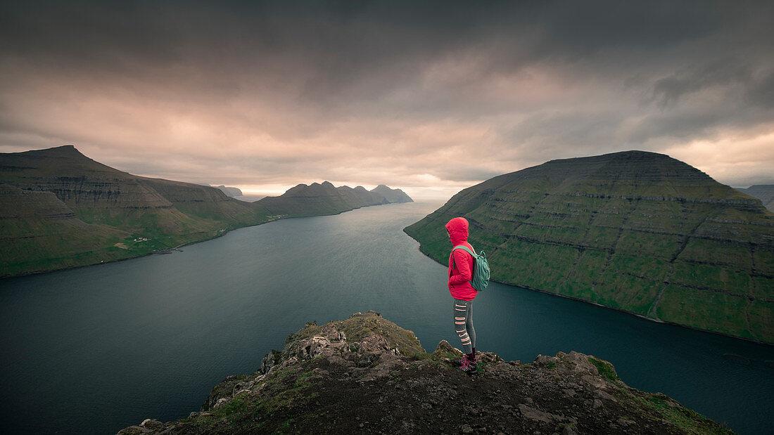 Frau am Aussichtspunkt Klakkur bei Klaksvik auf der Insel Bordoy mit Blick auf Kalsoy und Kunoy im Sonnenuntergang, Färöer Inseln