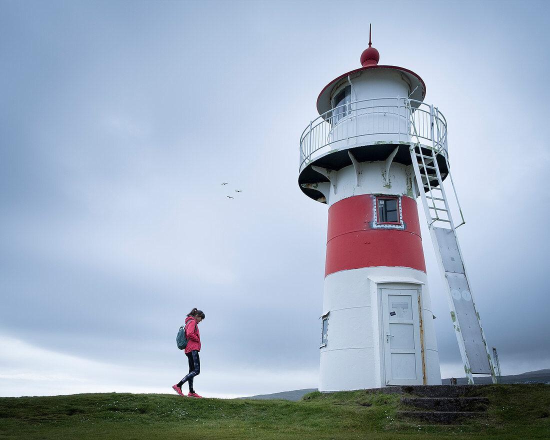 Frau am Leuchtturm Skansin in der Hauptstadt Torshavn, Färöer Inseln