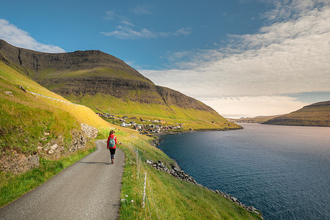 Frau wandert bei Sonnenschein beim Dorf Bour auf Vagar, Färöer Inseln