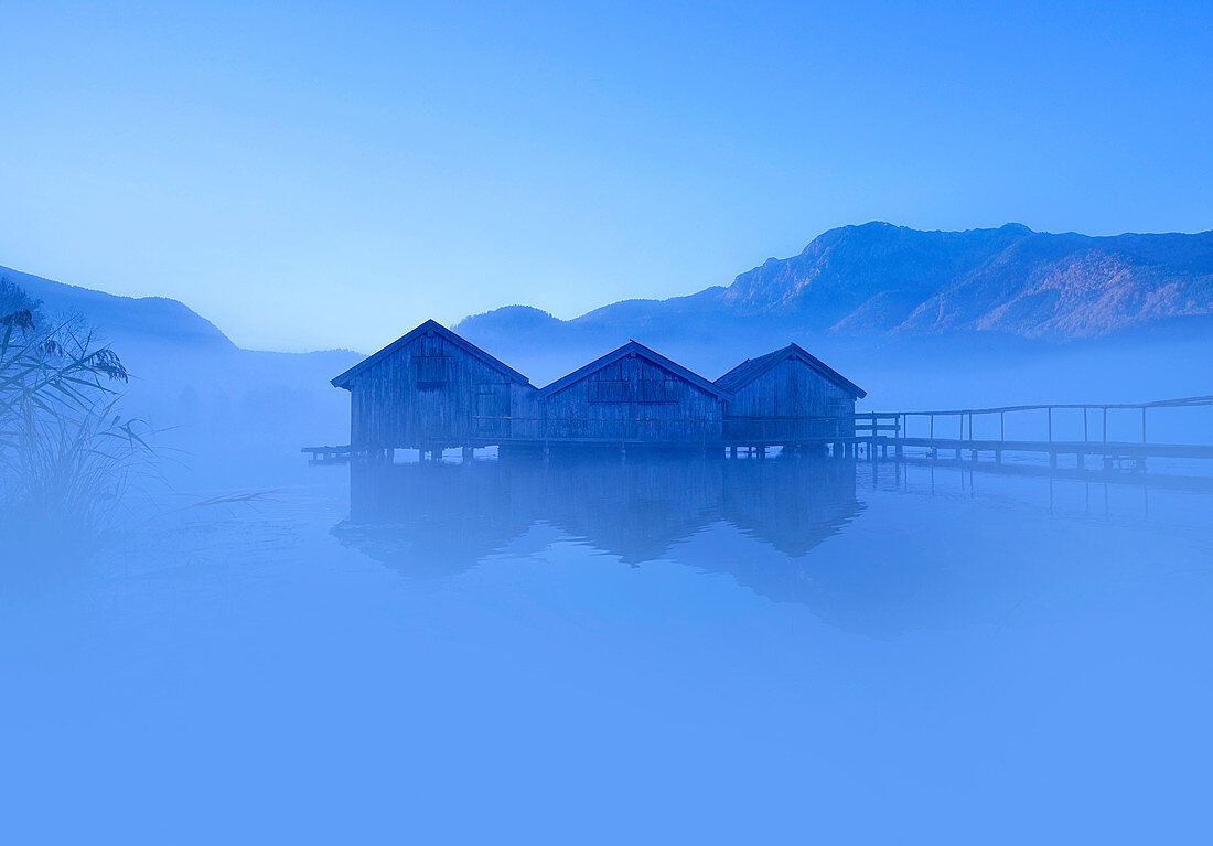 The fishing huts at Kochelsee in the morning mist, Bavaria, Germany; Europe