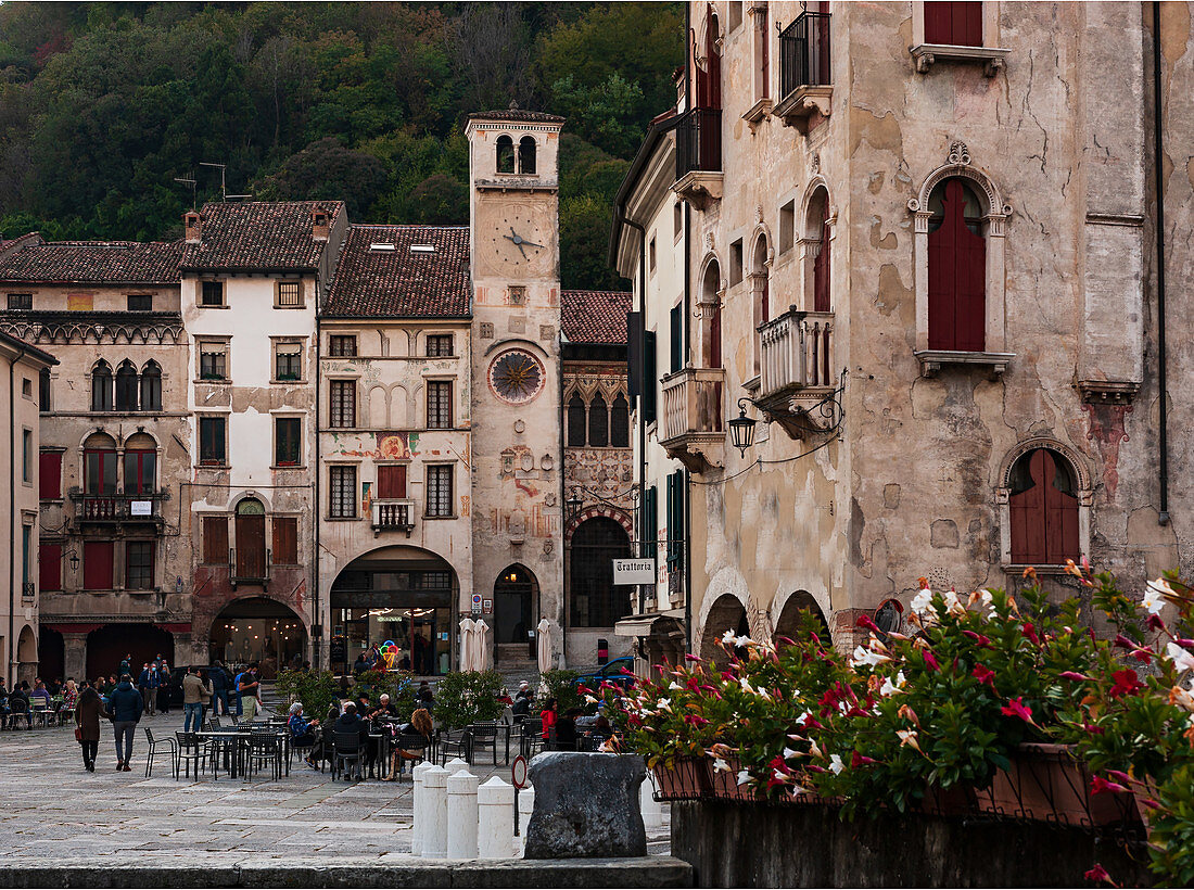 People in  Piazza Flaminio in the Serravalle district in Vittorio Veneto, in the background the Civic Tower and the Community Palace. Veneto region. Italy