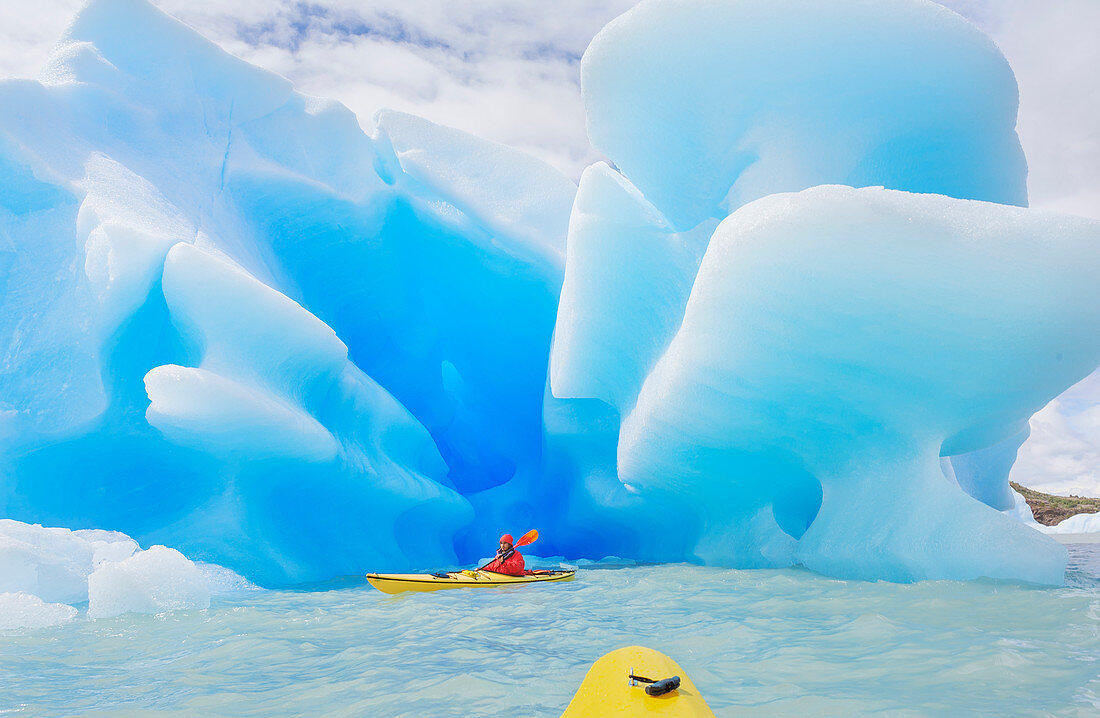 Kayaker paddling near icebergs, Torres del Paine National Park, Chile, South America