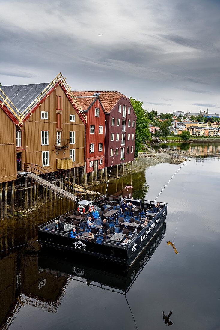 Pub, pub, restaurant Den Gode Nabo on pontoon terrace in front of old warehouses along the Nidelva, Trondheim, Norway