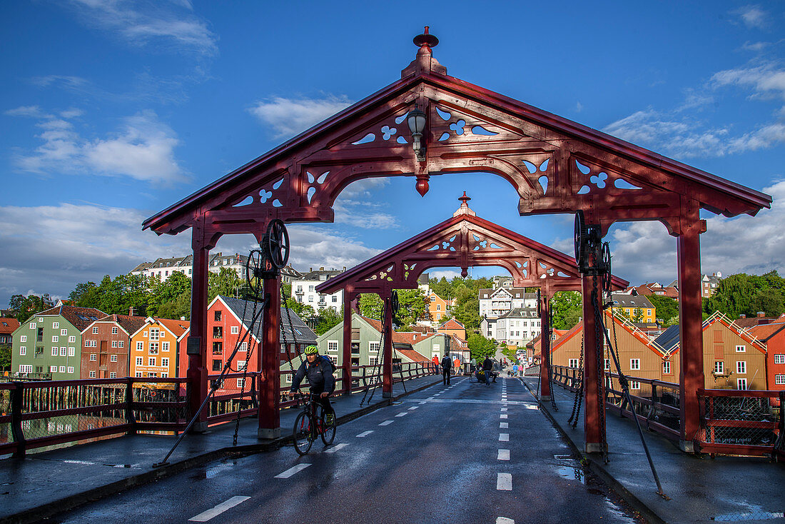 Cyclists on the Bybrua bridge on the Nidelv River with old warehouses, Trondheim, Norway