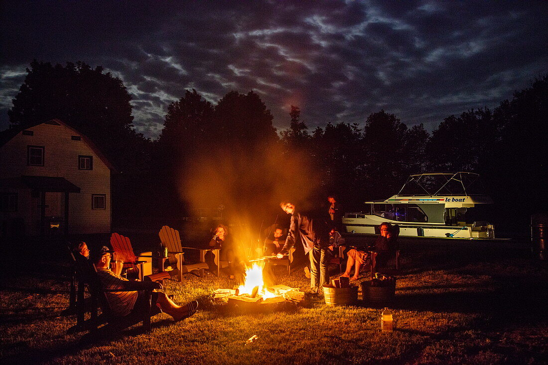 People relax by the campfire under the full moon at Parks Canada Campground at Beveridge Locks on the Tay River with a docked Le Boat Horizon houseboat at night, near Lower Rideau Lake, Ontario, Canada, North America