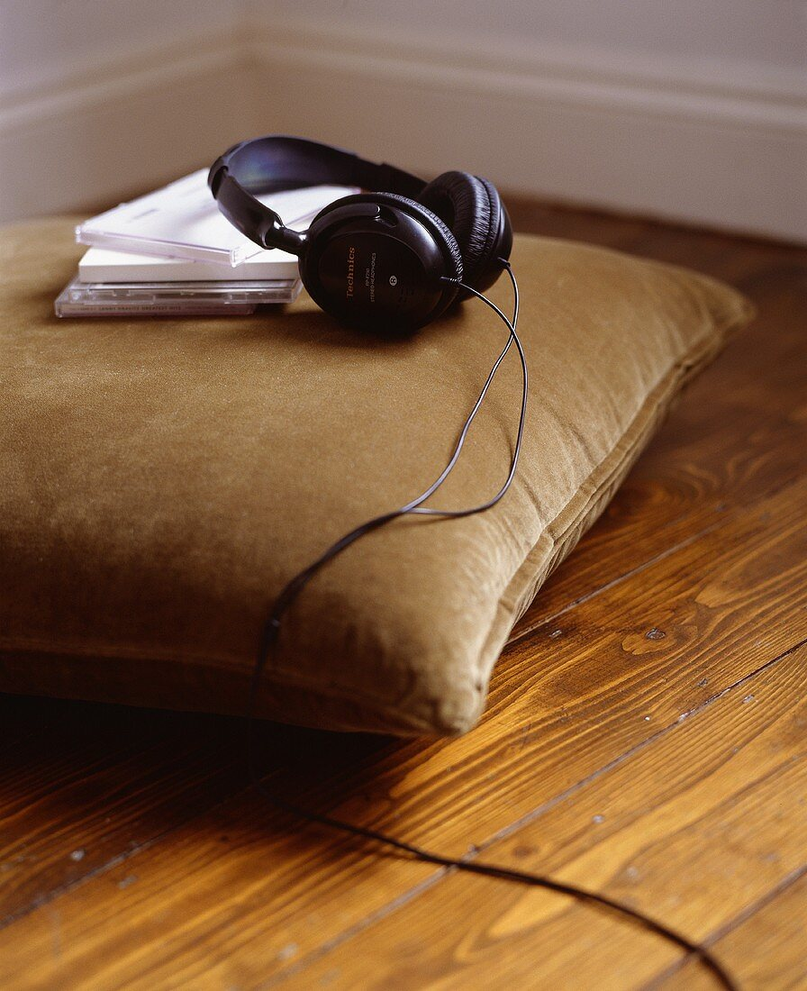 Headphones and CDs on a cushion