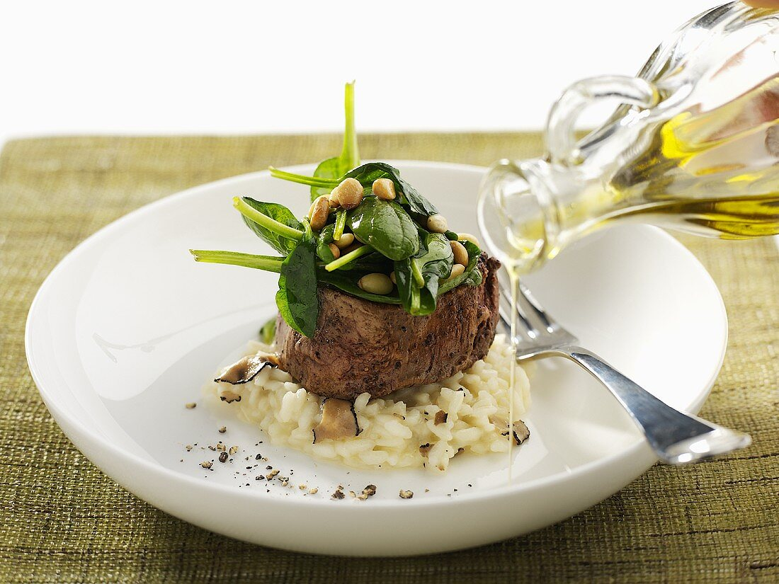 Drizzling olive oil over beef fillet on mushroom risotto