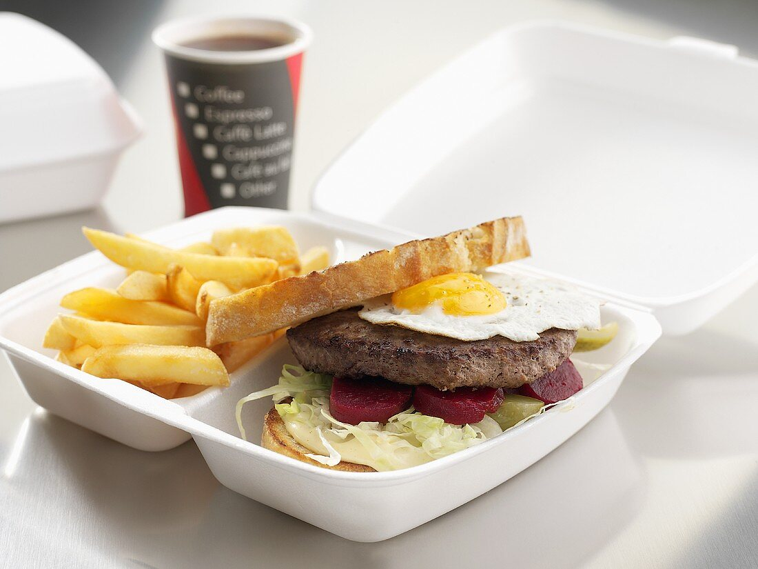 Hamburger with fried egg and chips to take away