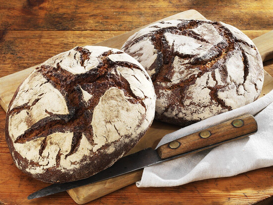 Two rustic country loaves on a chopping board