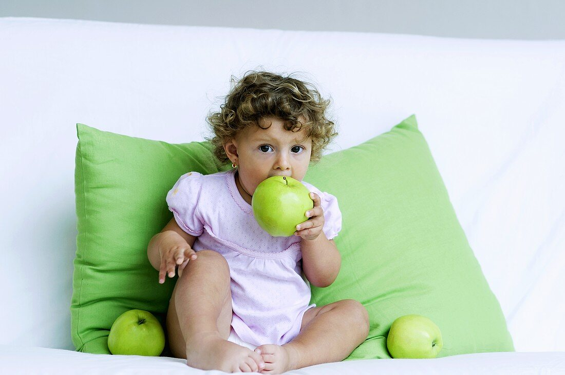 A little girl biting into a green apple
