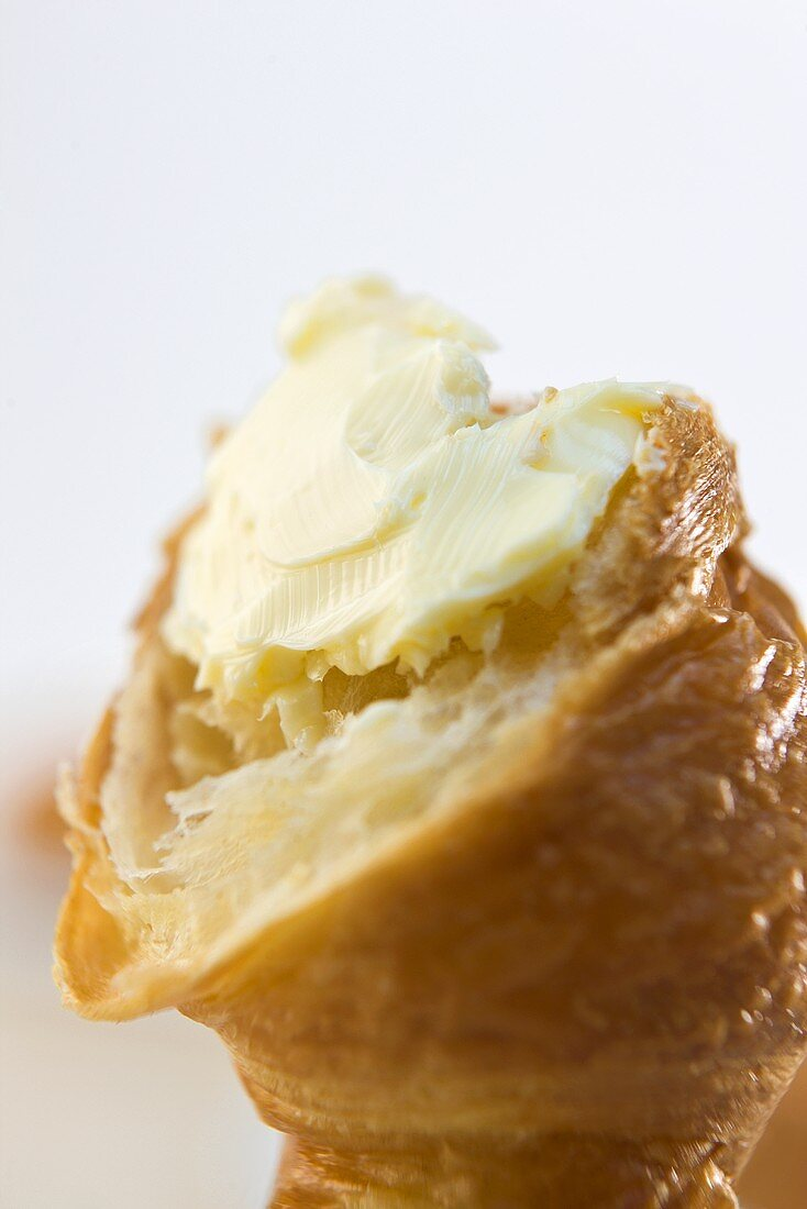 A croissant with butter (close-up)