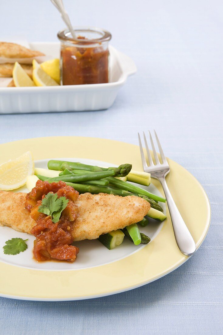 Breaded fish fillets on a bed of green vegetables