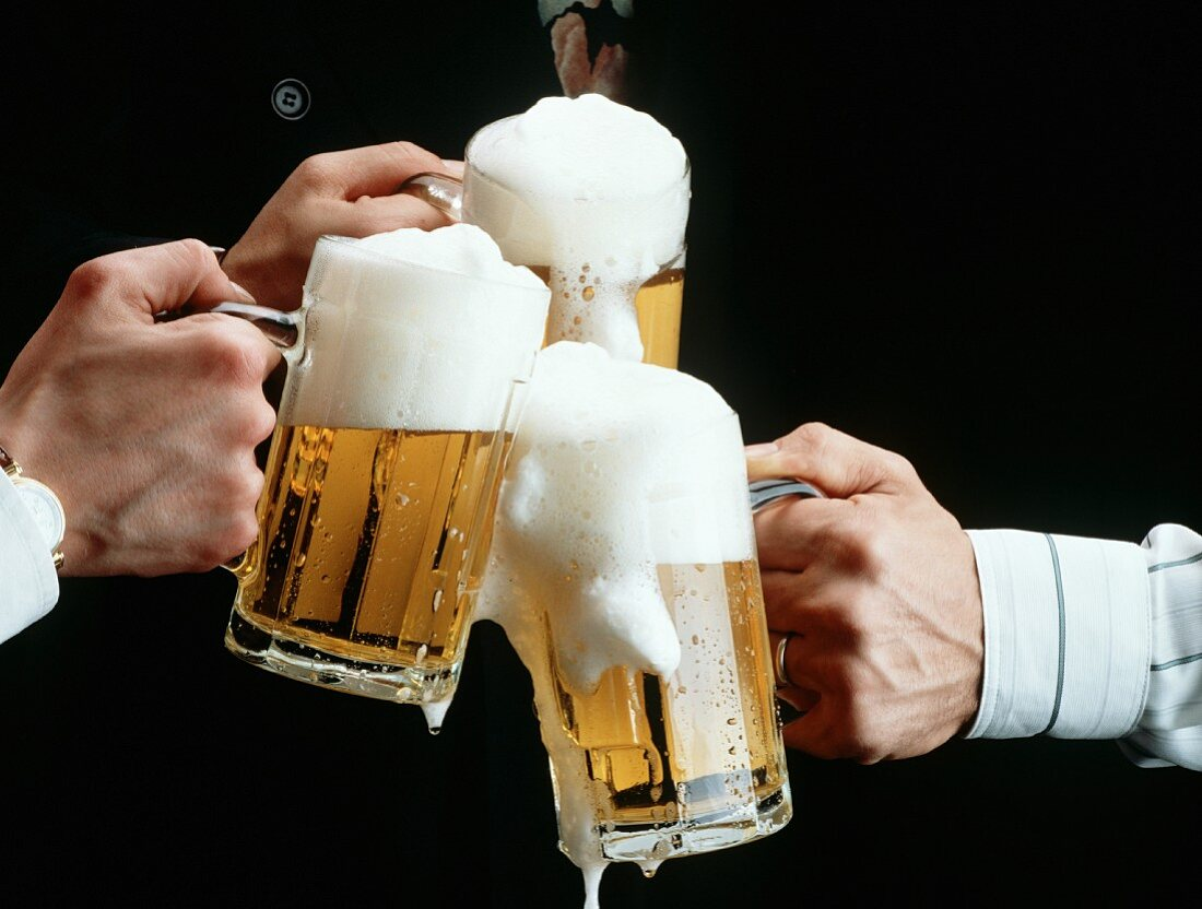 Three Mugs of Beer Clinking in a Cheer