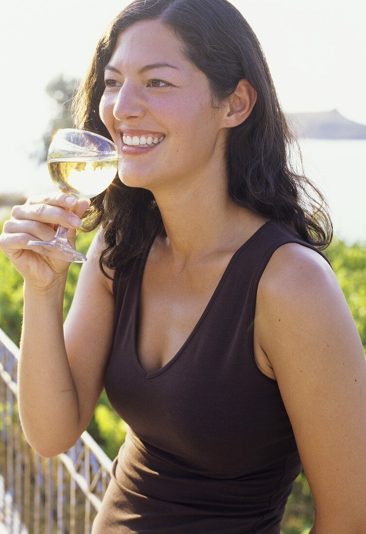Young woman with white wine on terrace