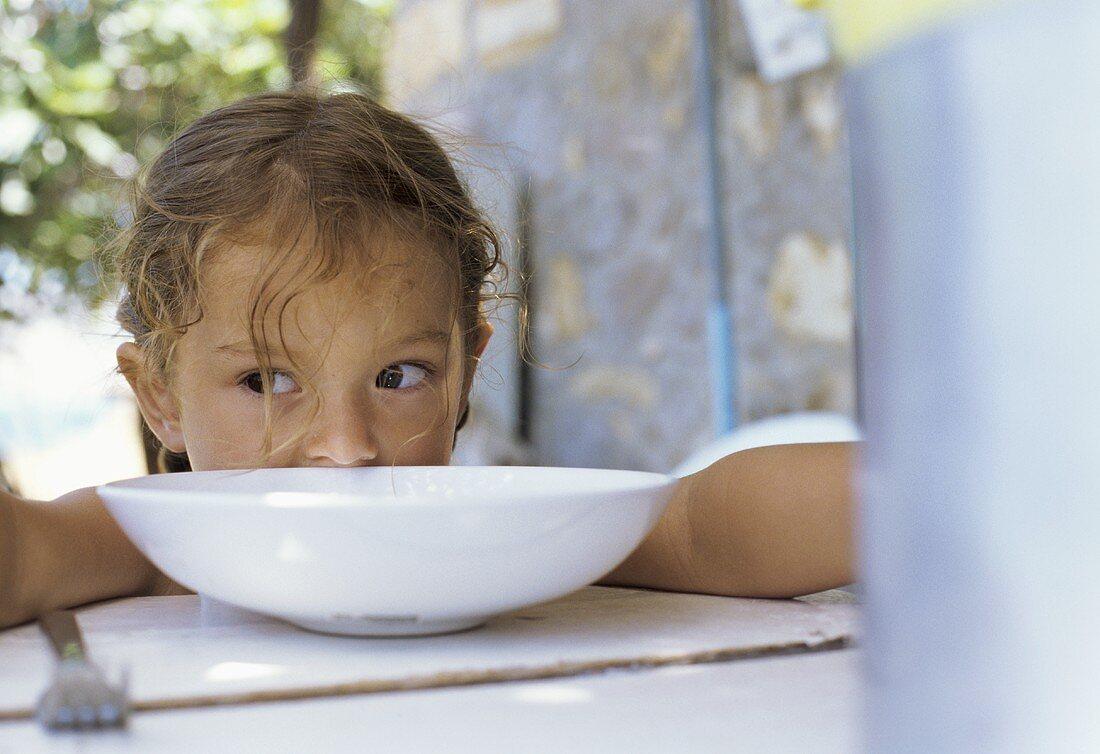 Girl half-hidden behind a white bowl