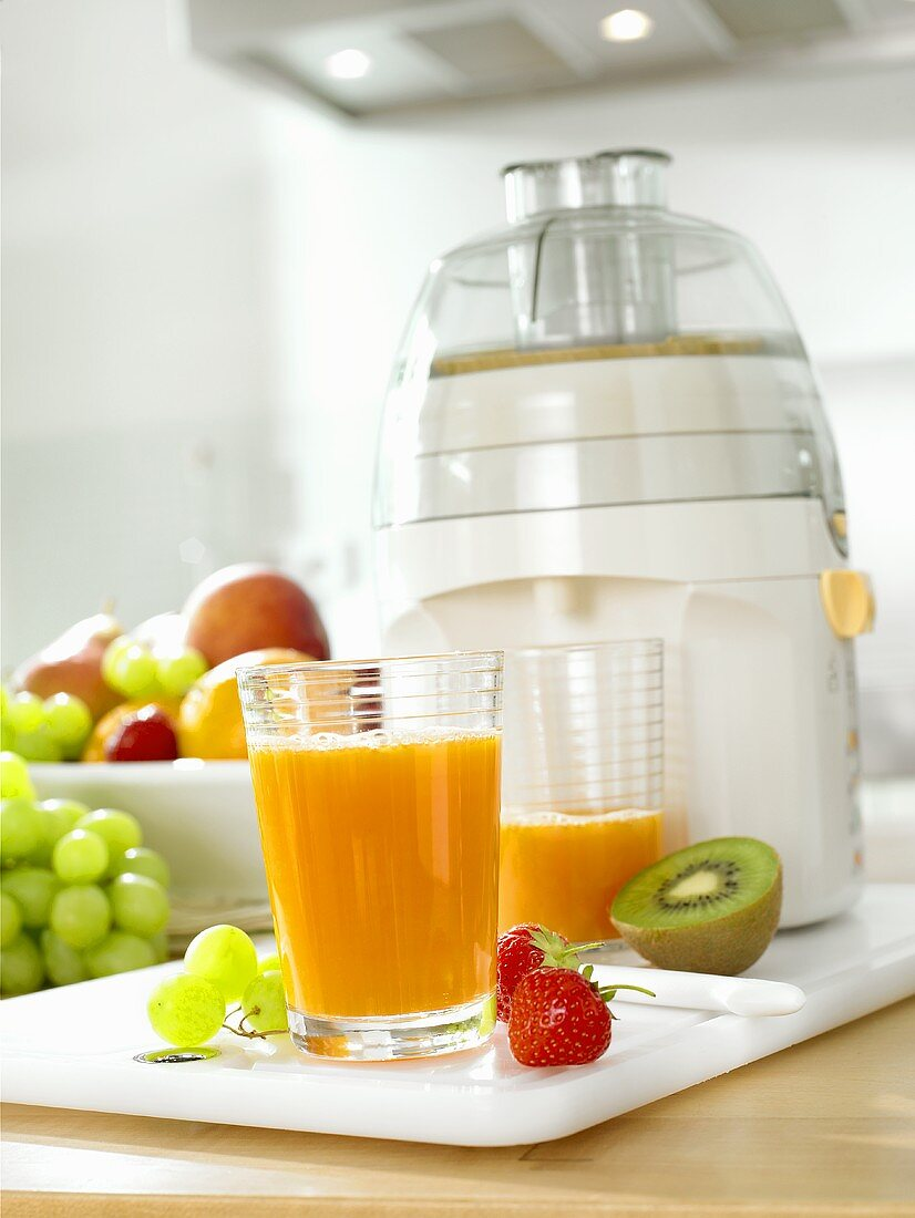 Multivitamin juice in glasses in front of electric juicer