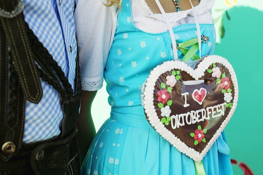 Woman in national dress with Lebkuchen heart (Oktoberfest, Munich)