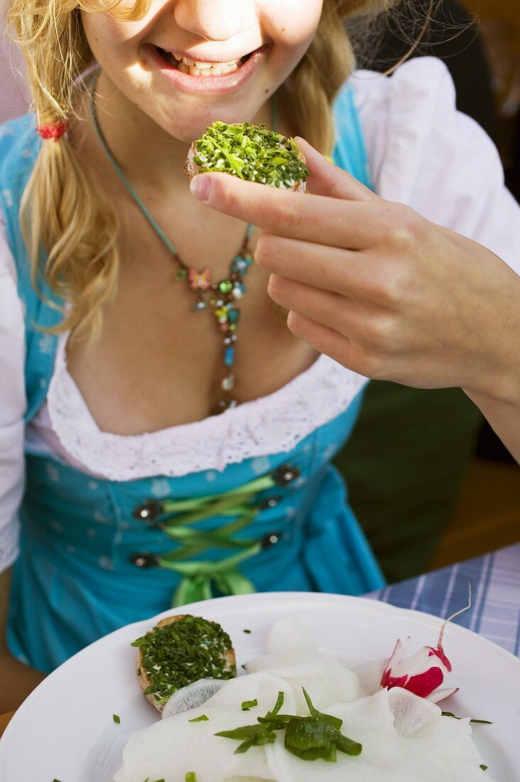 Girl eating bread and chives in a beer garden