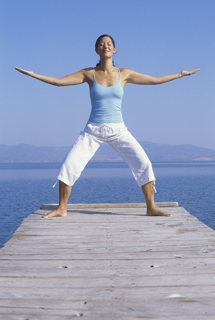 Woman in yoga posture by the sea