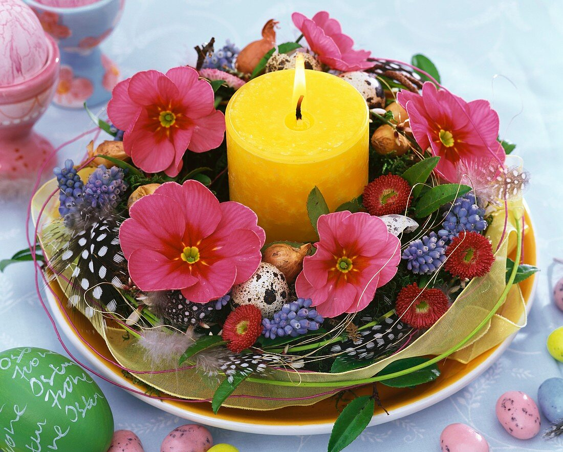 Easter wreath with primulas and burning candle