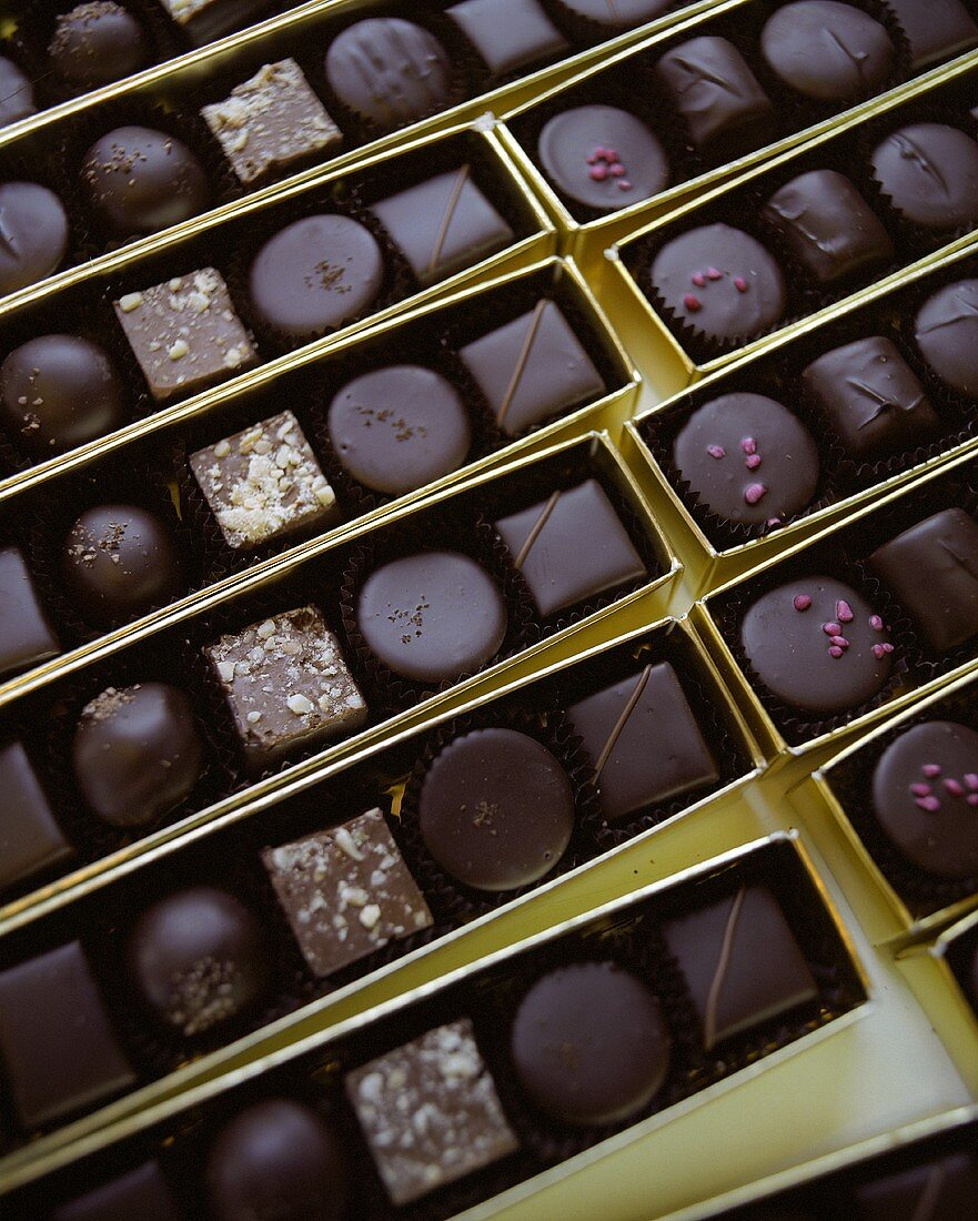 Assorted chocolates in gold boxes