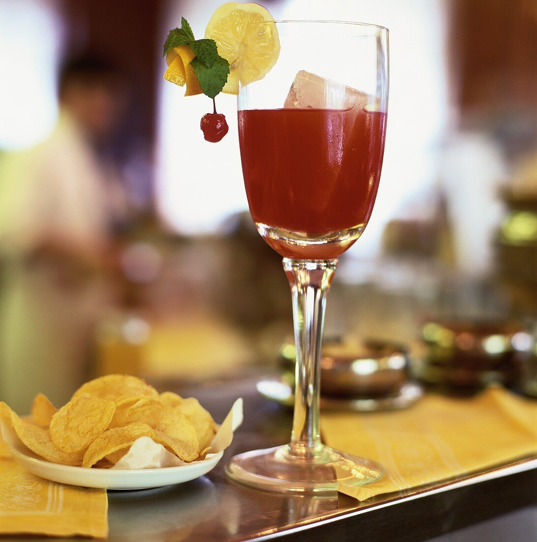 Fruity drink and crisps in a bar