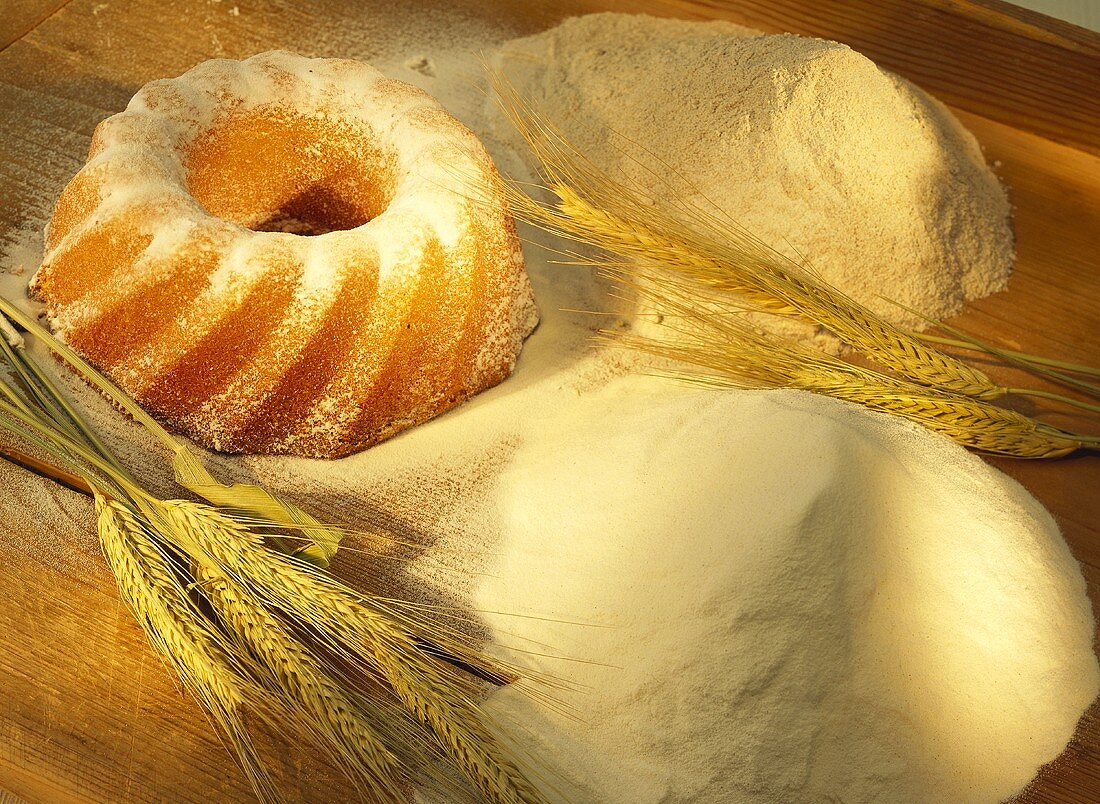 Still life with flour, cereal ears and gugelhupf