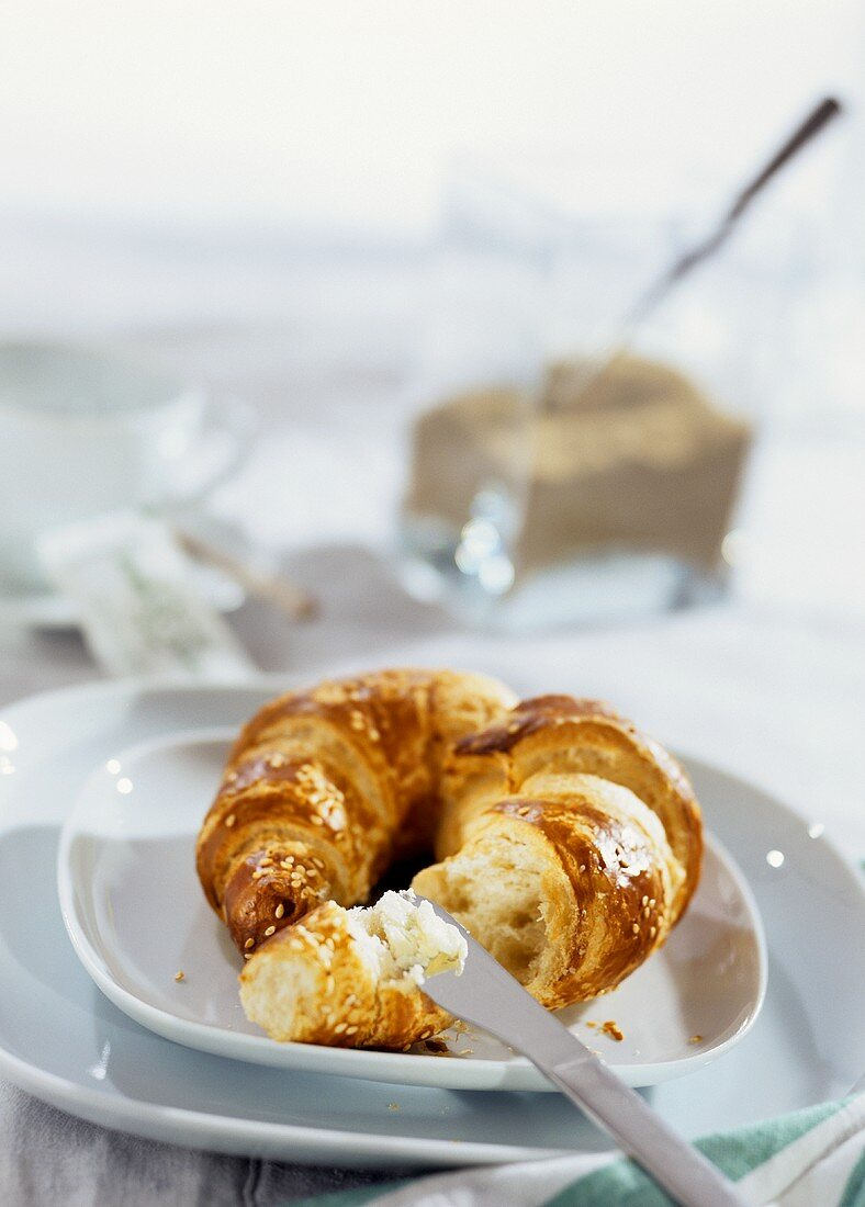 Sesame croissant with butter and knife