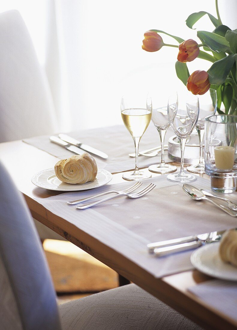 Laid table with yeast baking, white wine and tulips