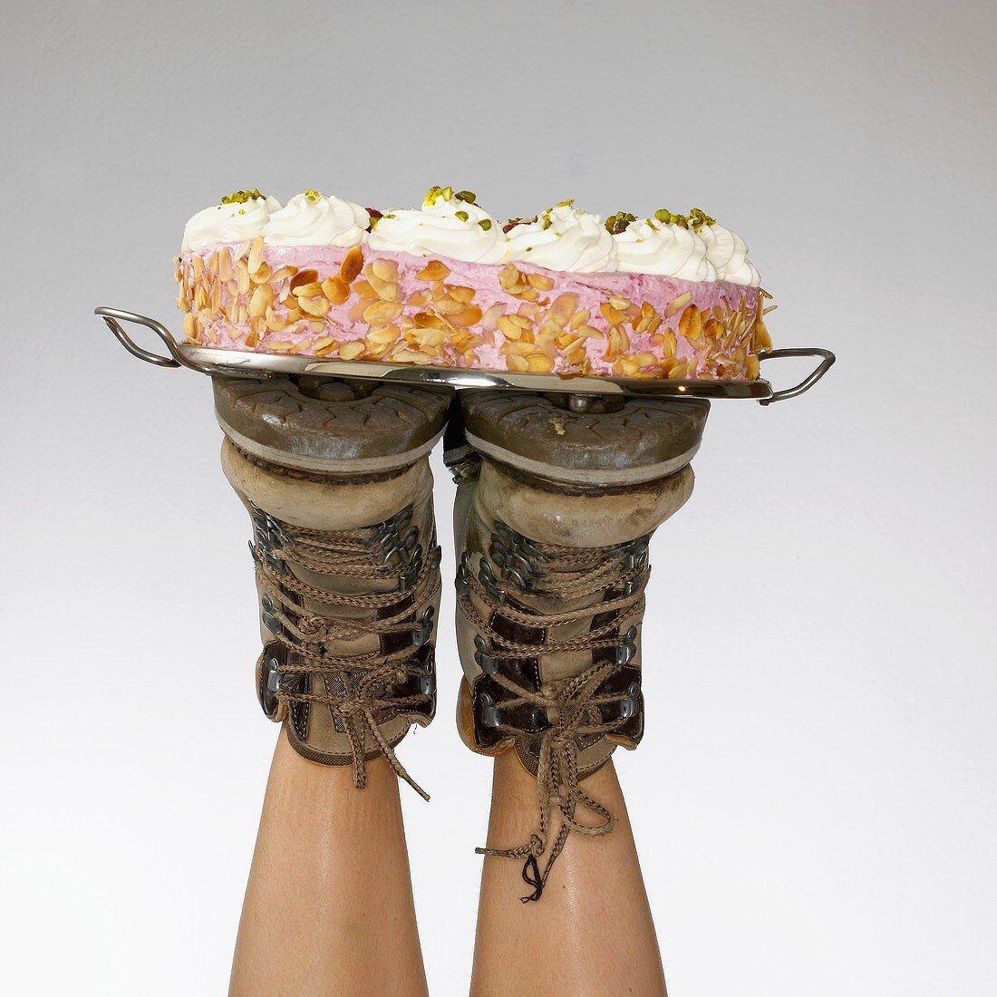 Two feet balancing a cream cake on a tray