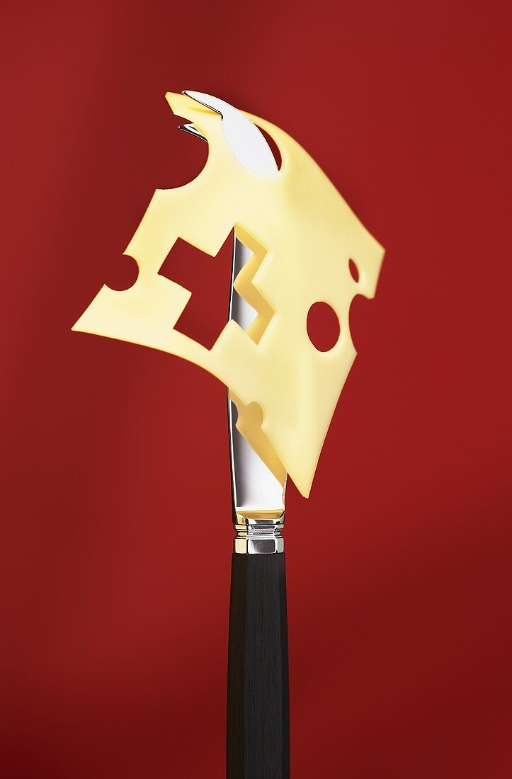 Symbolic picture with Swiss cheese and cheese knife
