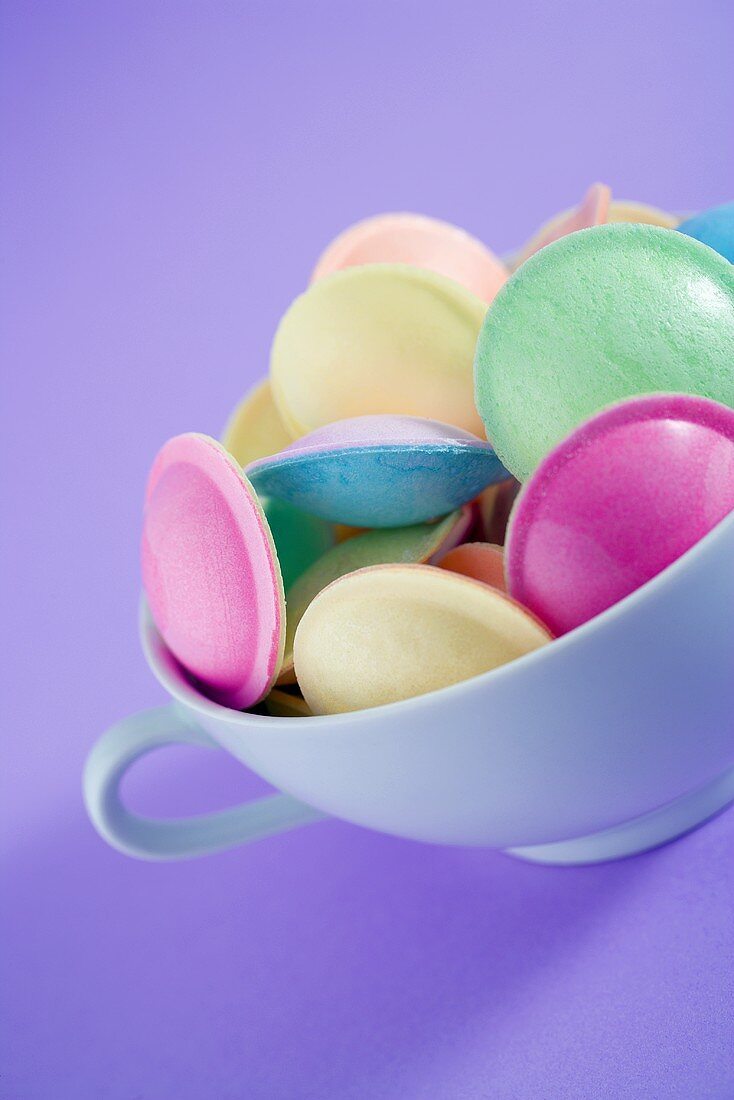 Pastel-coloured flying saucers in a cup