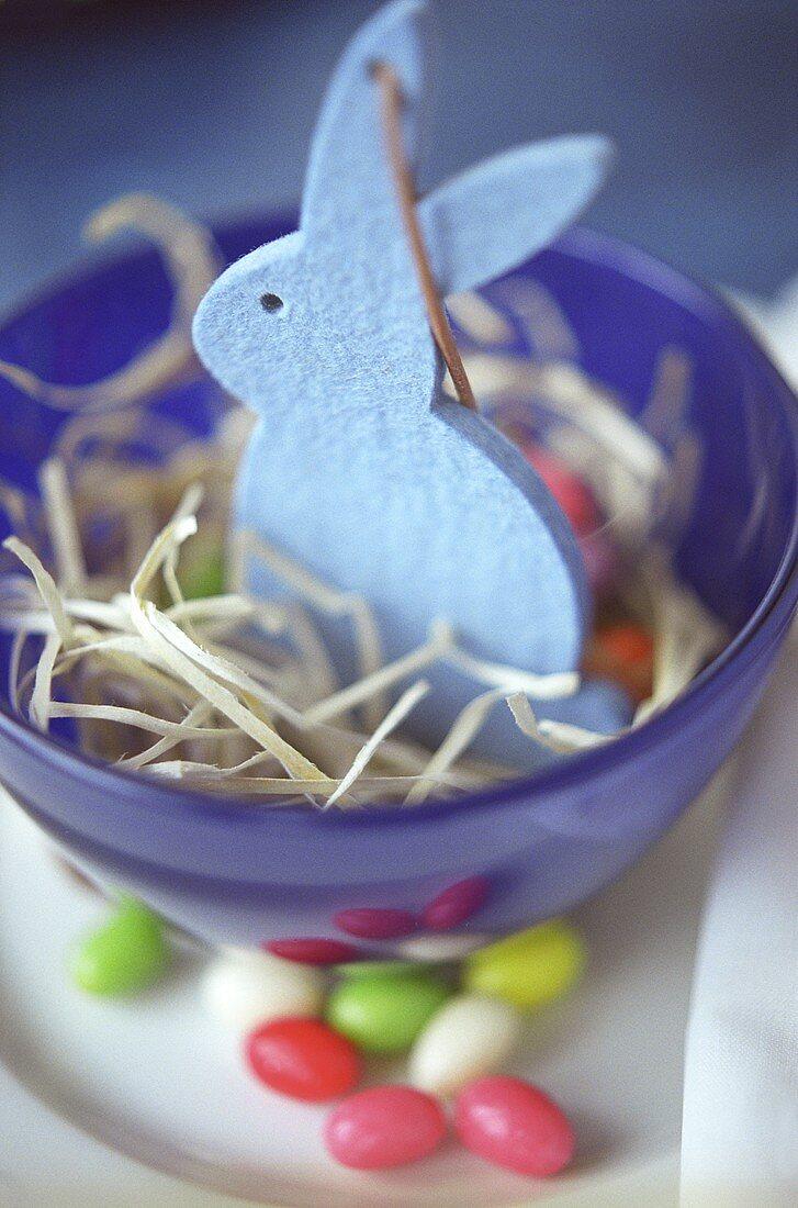 Blue felt bunny in a bowl of straw