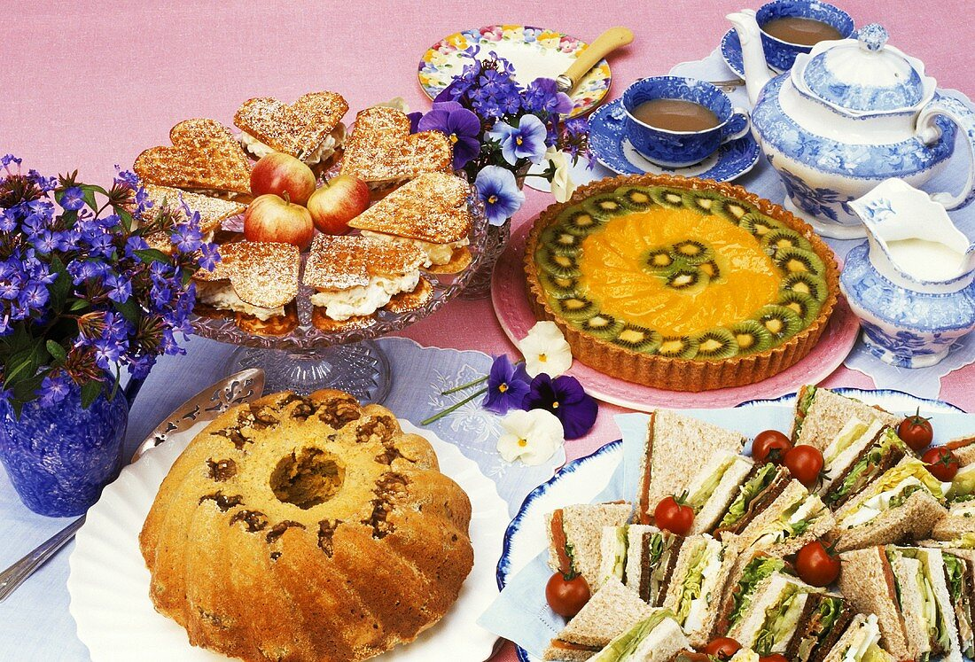 Sandwiches, cakes and waffles with tea