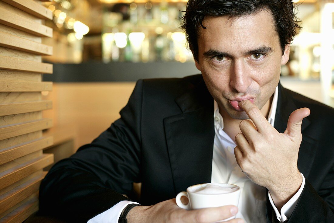Man licking milk froth from his finger