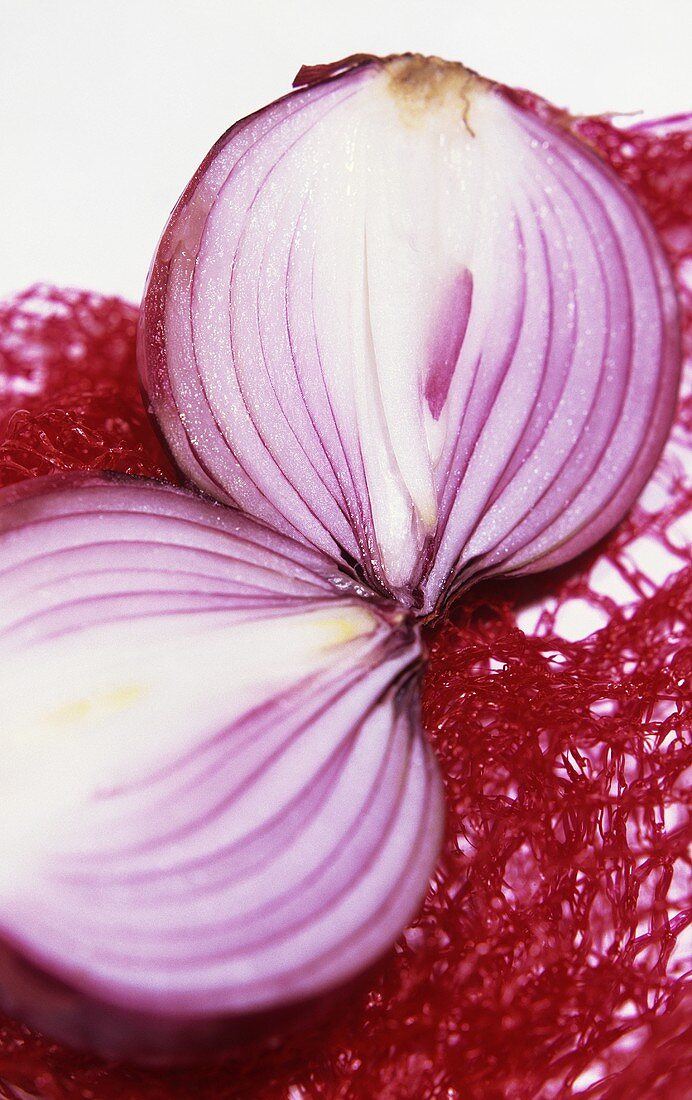 A halved red onion on a net