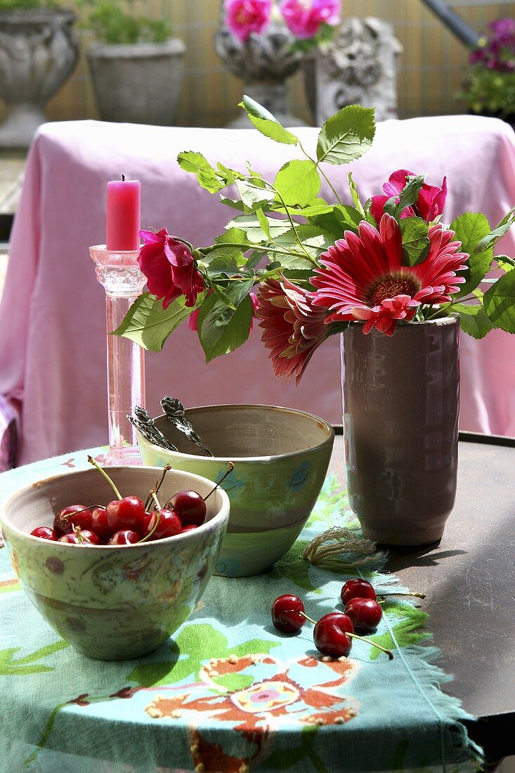 A small bowl of cherries and vase of flowers on a table