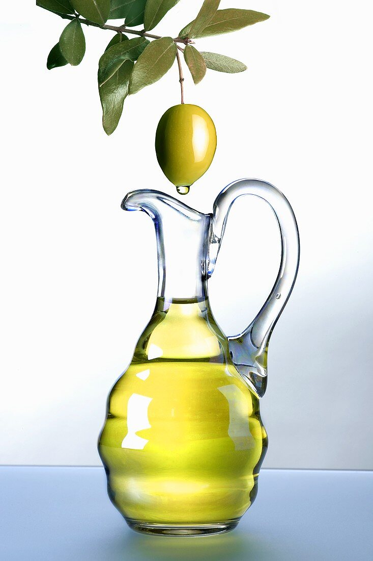 Olive oil dripping from an olive into a carafe