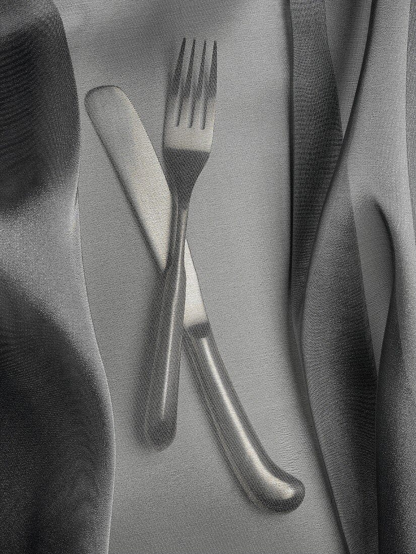 Knife and fork under a fine cloth