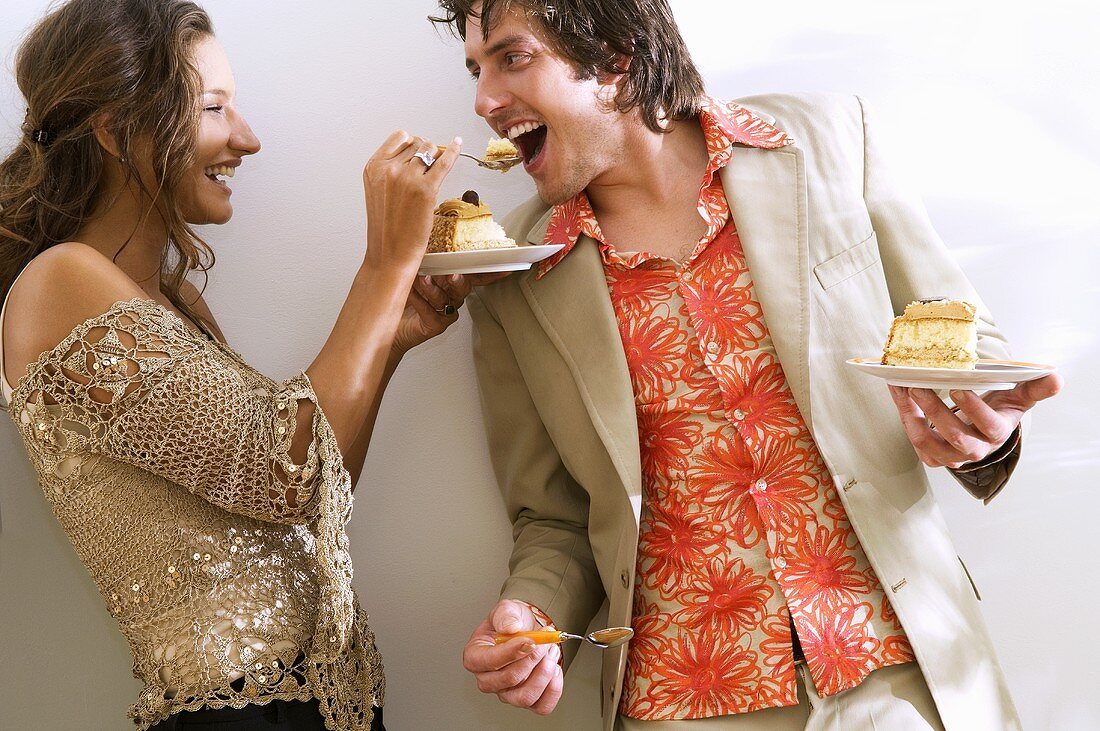Young woman feeding cake to man