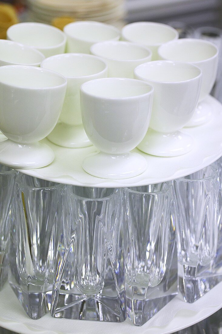 Tray of eggcups on top of tray of flower vases