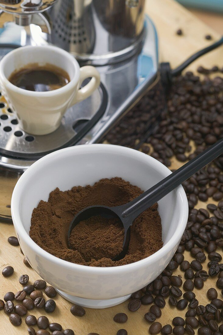 Cup of espresso, espresso machine, ground coffee, coffee beans