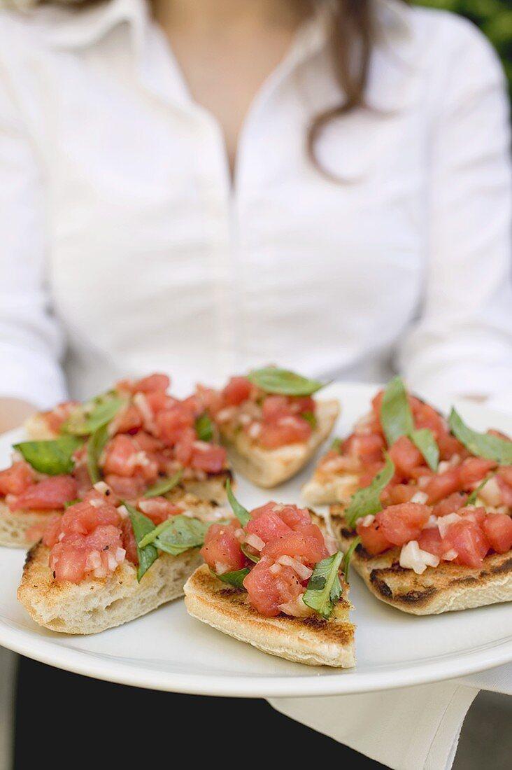 Waitress serving bruschetta with tomato salsa