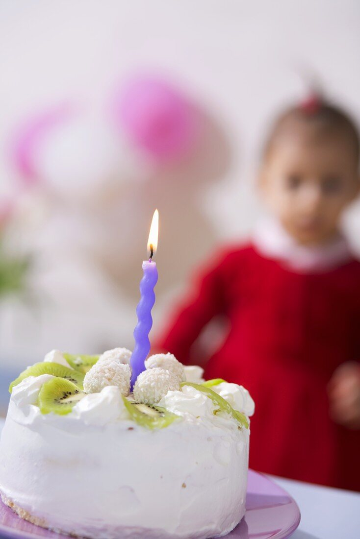 Small kiwi coconut cake with one candle, child in background