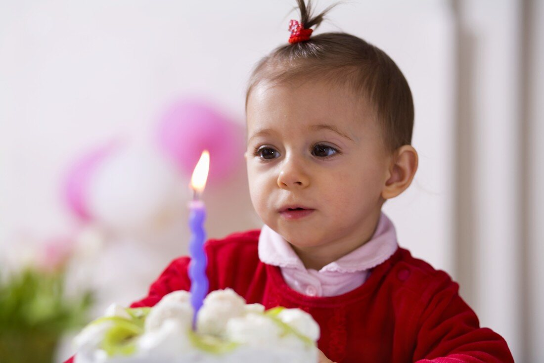 Small girl blowing out candle on kiwi coconut cake