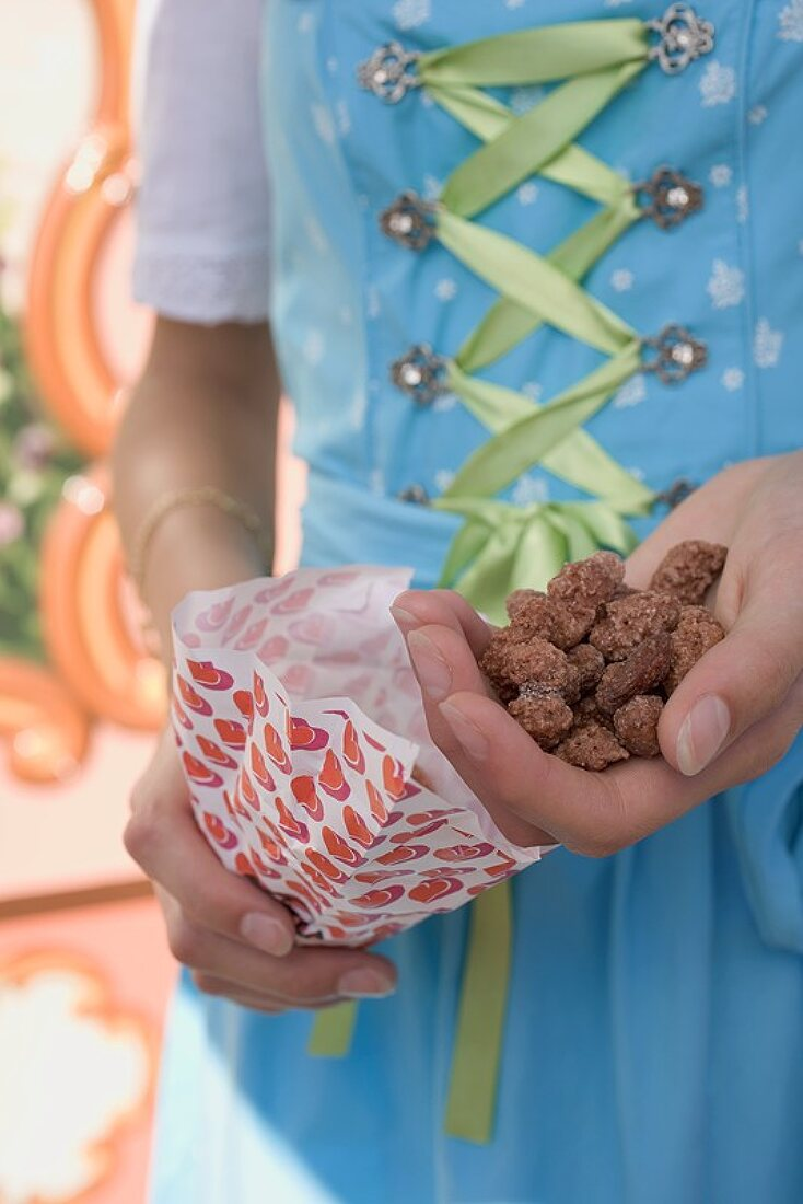 Girl in German national dress holding roasted almonds (Oktoberfest)
