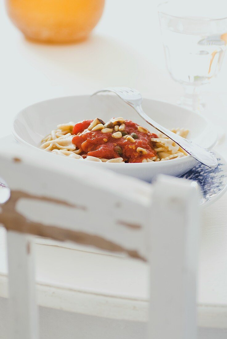 Wholemeal farfalle with tomato sugo, capers and pine nuts