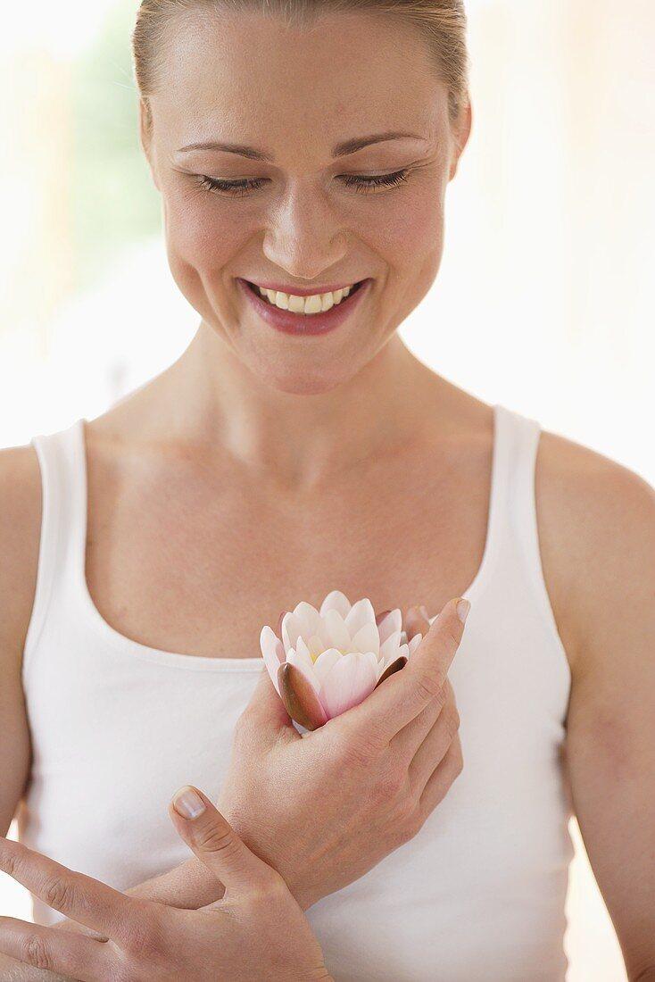 Smiling woman holding lotus flower